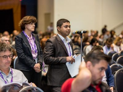 Attendees participating in the Q&A portion of a major symposium