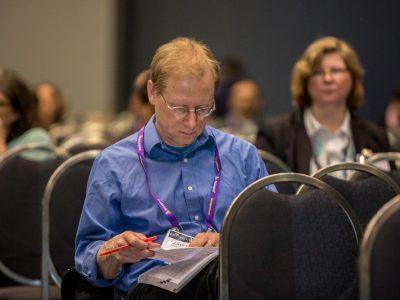 Michael Farrar flipping through the annual meeting program
